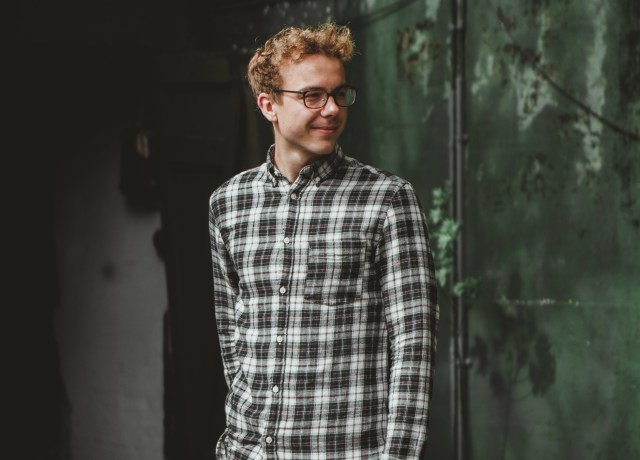 man in blue and white plaid dress shirt standing beside green wall