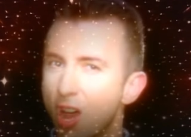 Marc Almond singing with his face superimposed on a space background
