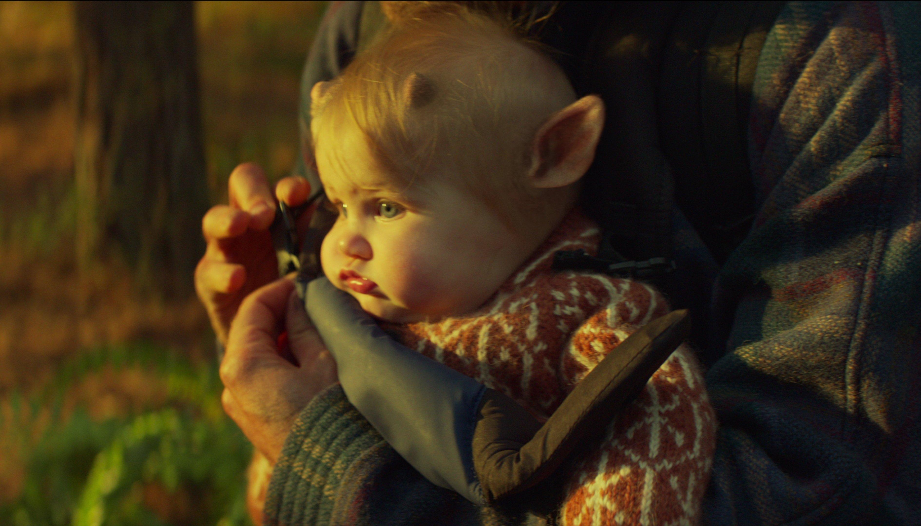 Um bebê com pequenos chifres e orelhas de veado