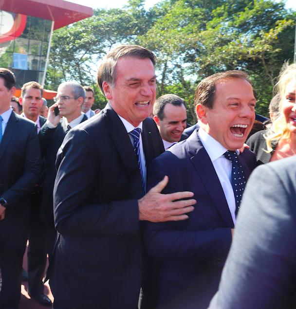 Bolsonaro abraçando Dória por trás e ambos rindo