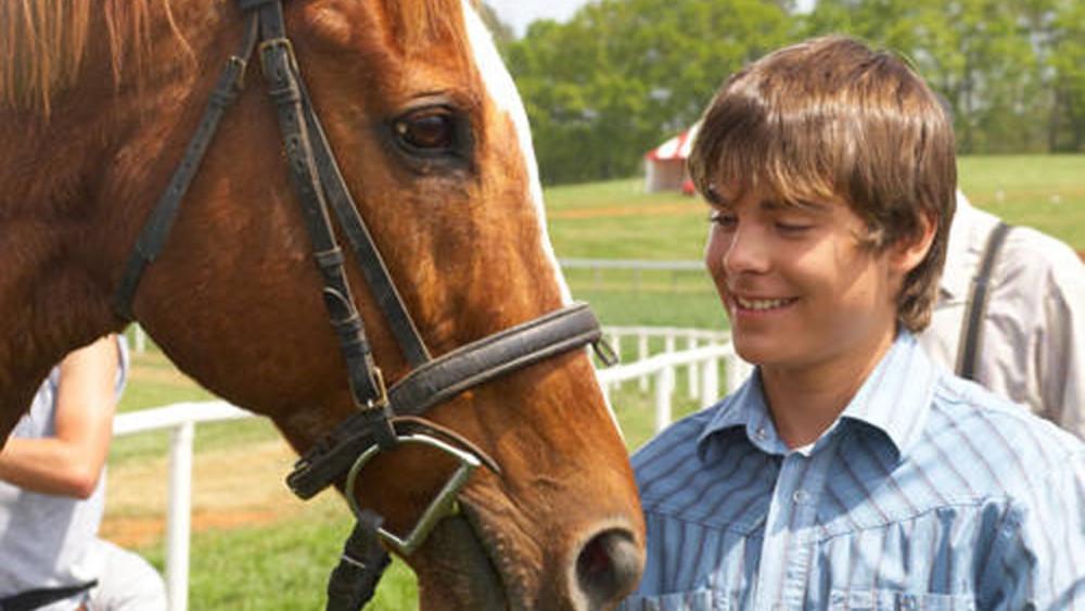 Zac Efron mexendo em cavalo
