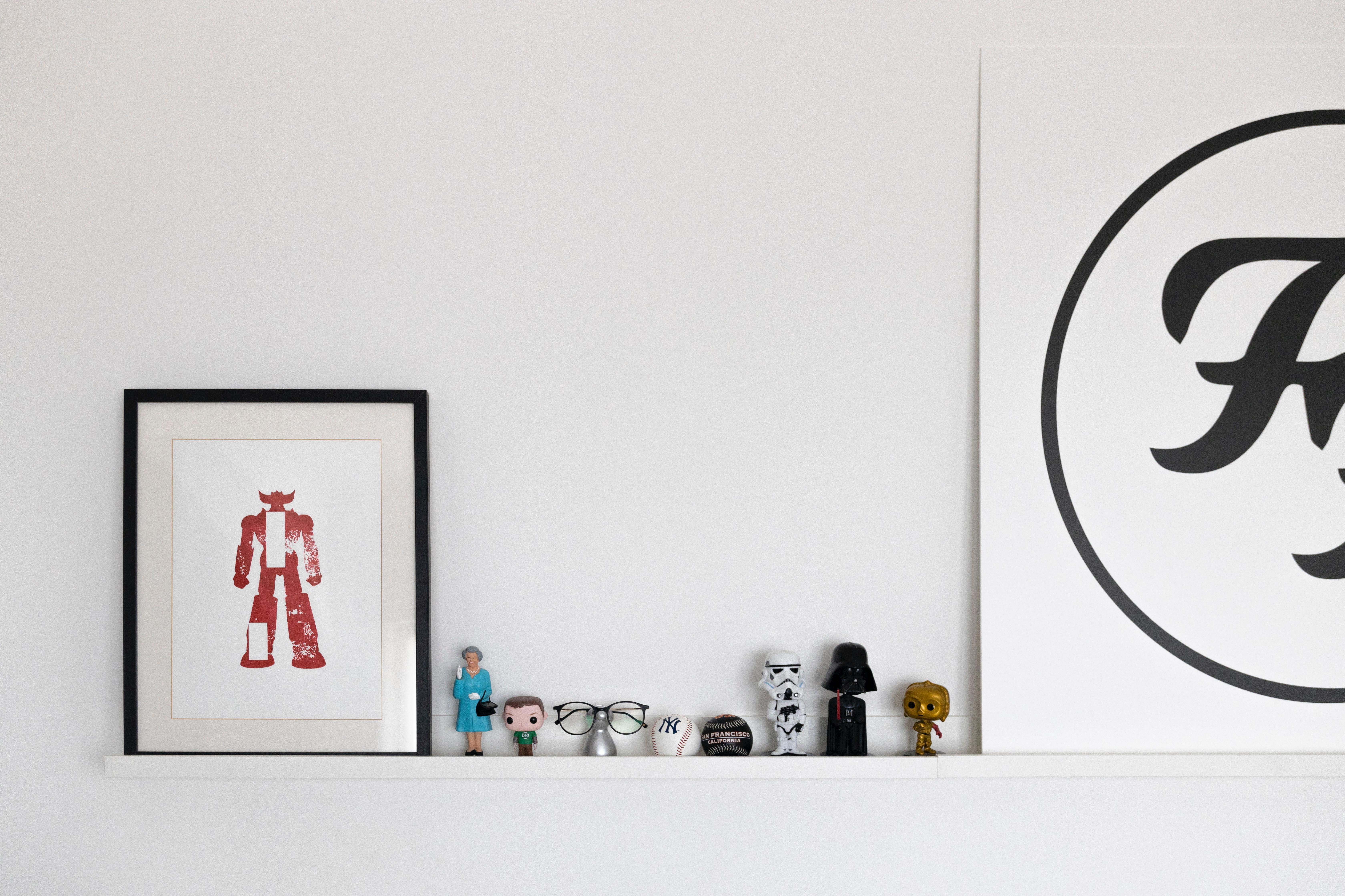 Uma prateleira com bonecos de filmes, óculos e um disco do Foo Fighters