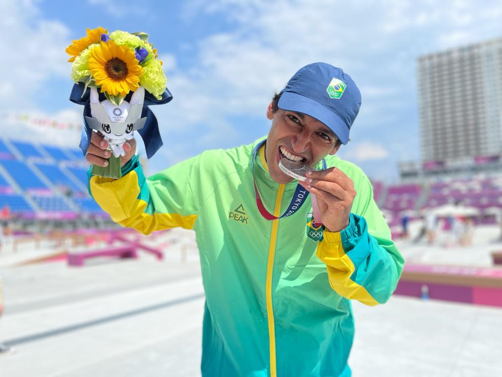 Kelvin Hoefler mordendo a medalha de prata que ganhou em Tóquio