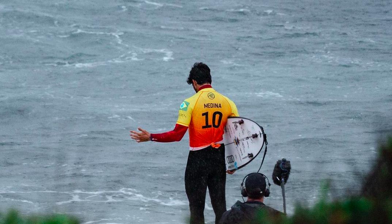 Gabriel Media de costas, olhando para o mar, usand o uniforme da Seleção de Surf brasileira. Logo embaixo dele há um homem com microfones gigantescos.