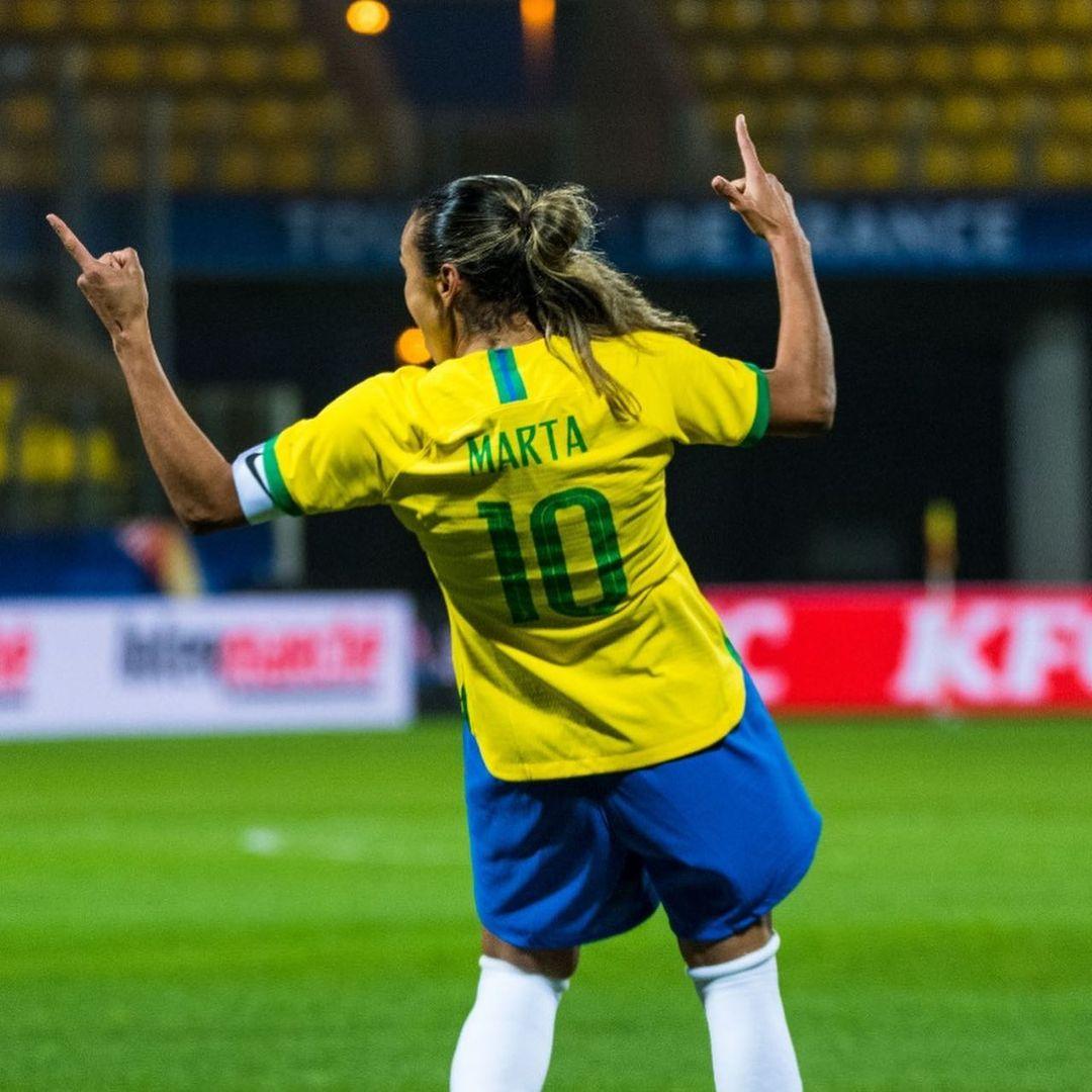 Marta, de costas, usando o uniforme da Seleção, apontando com os dois dedos indicadores para cima.