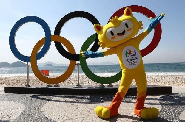 Vinícius, de braços abertos, na frente de uma escultura com os arcos olímpicos - no Rio.