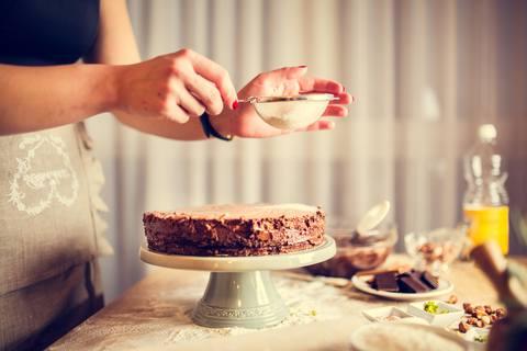 woman in black cardigan holding chocolate cake