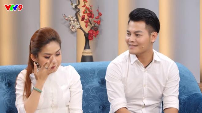 Nhật Minh nhìn vợ cười âu yếm khi cô rơi nước mắt nhớ lại quãng thời gian khó khăn đã qua.