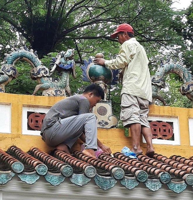 Các thợ thủ công đã gắn trái châu gần 100 tuổi trên nhà văn bia chiều 12-9 (ảnh do Ban Quản lý di tích lịch sử văn hóa lăng Lê Văn Duyệt cung cấp)
