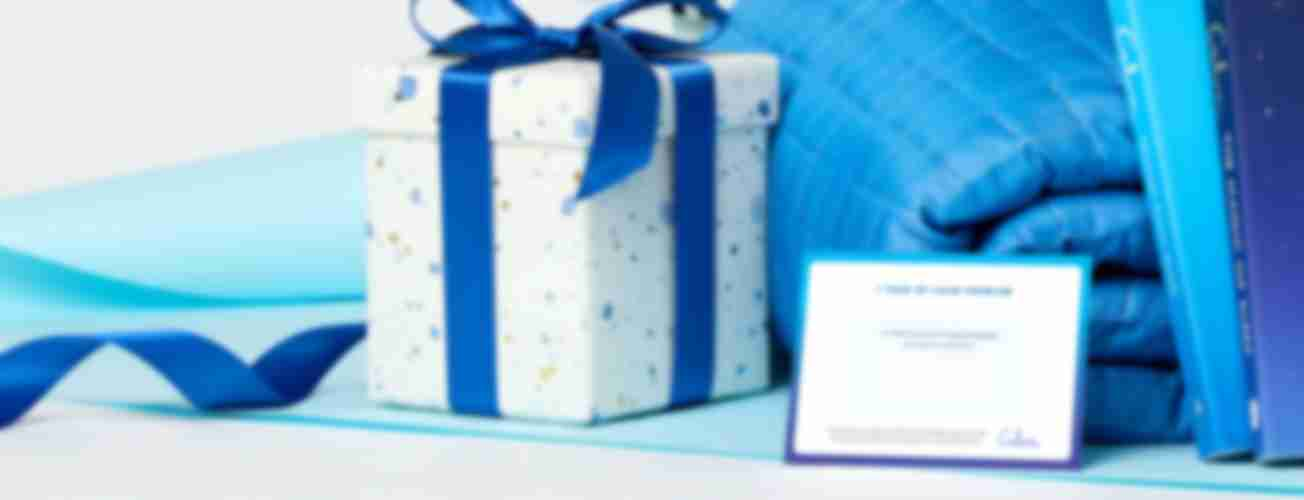 A photo of a wrapped present with a gift certificate next to it that reads '1 Year of Calm Premium'