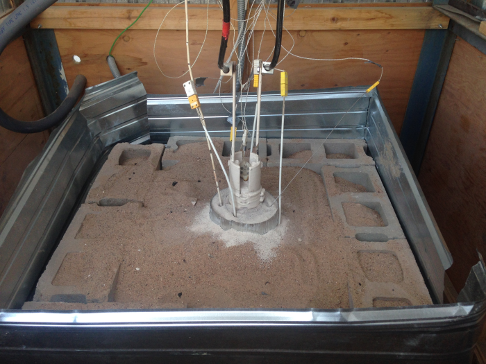 Laboratory test—Host rock has 4-inch drilled core hole and is buried in sand to stabilize temperatures and retain heat.