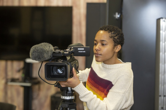 A female student behind a video camera