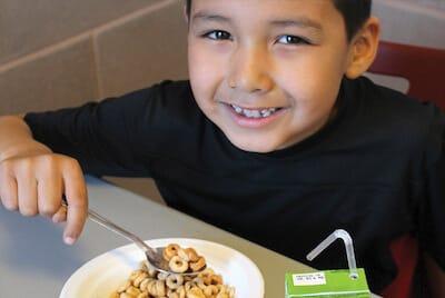 Indigenous boy eating a school breakfast