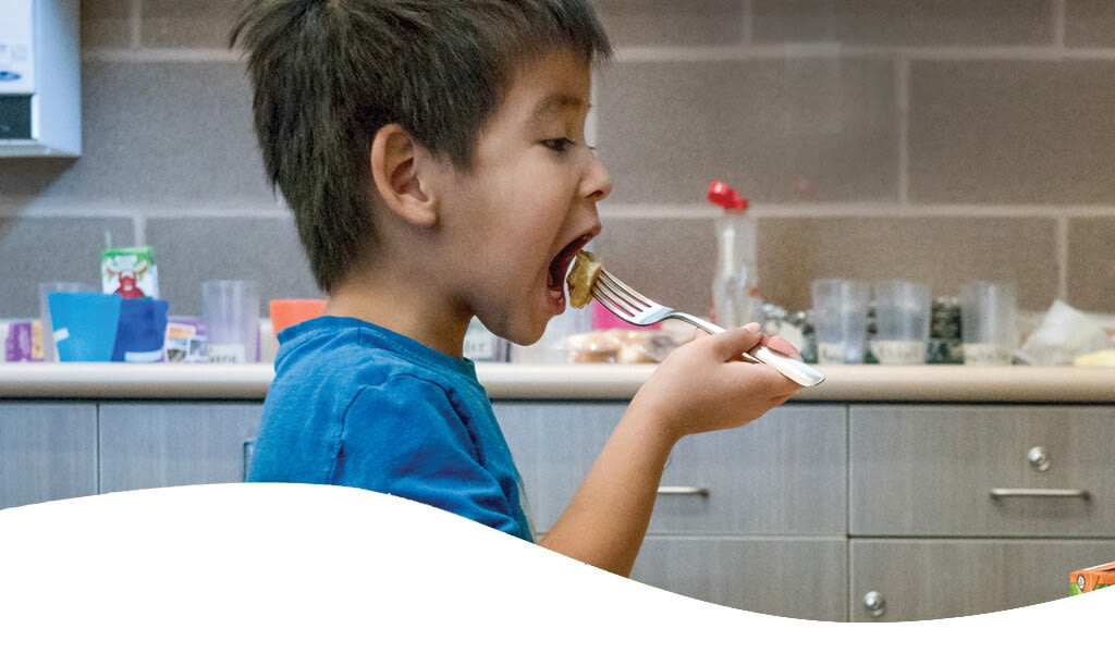 Indigenous boy eating a school meal