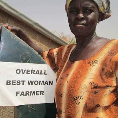 Madam Azuma stands with her Overall Best Woman Farmer award