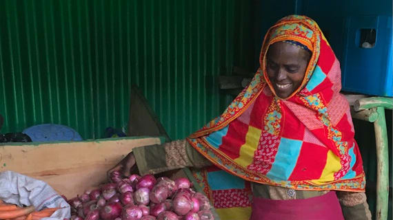 women standing in front of her produce for sale
