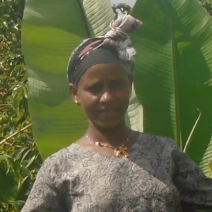Berhane, a female farmer from Ethiopia, stands in front of a banana tree