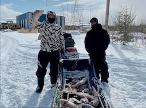 Two men stand beside a pile of fish they caught in Birch Narrows, Canada