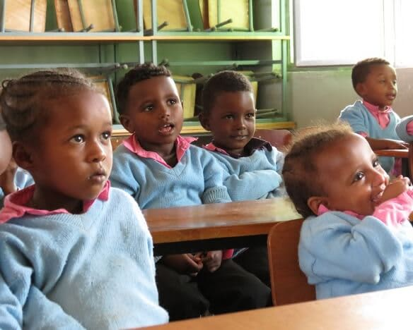 young children sitting at desks in a classroom in Ethiopia