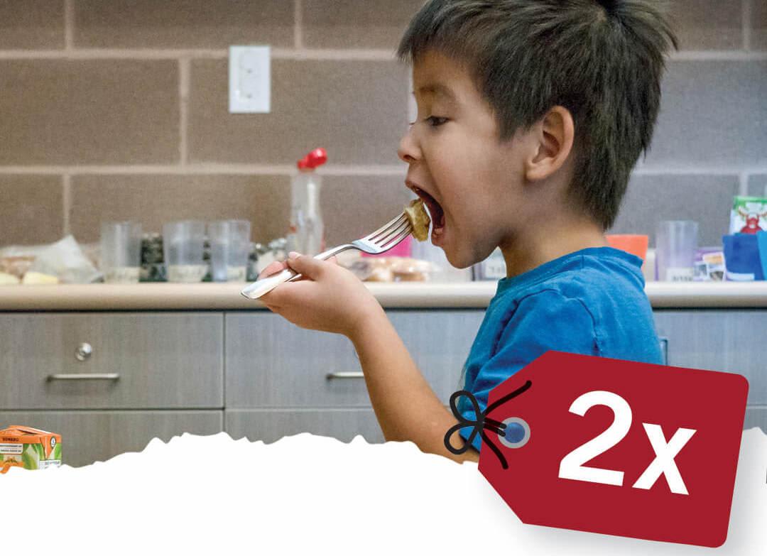 Charity Gifts Canada include school meals. Image shows First Nations boy enjoying his school breakfast.