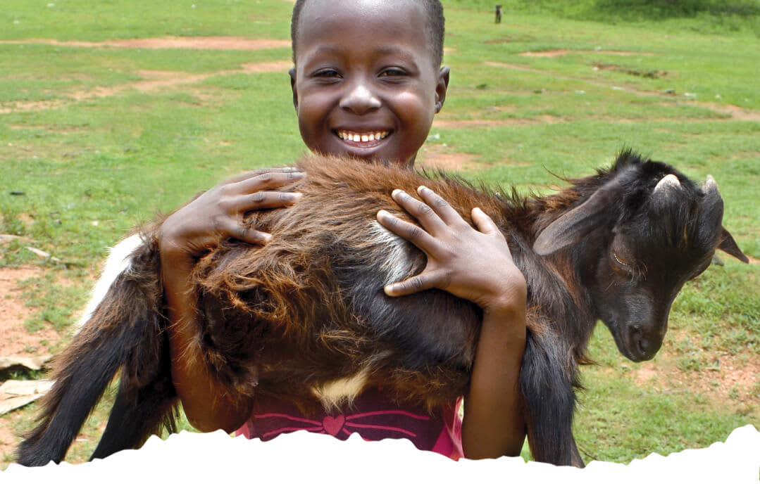 When you buy a goat for a family in Africa real families benefit. Image shows African girl holding a goat.