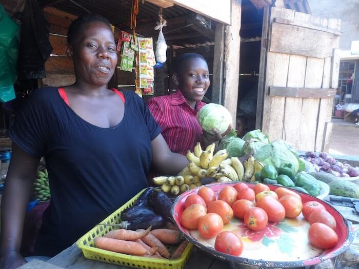 Gertrude and her daughter stand behind their fruit and veg stall