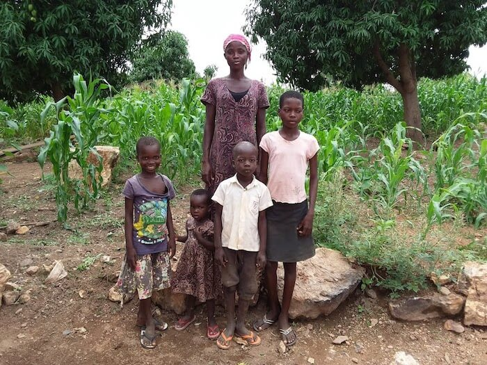Prudence stands outside together with her four children