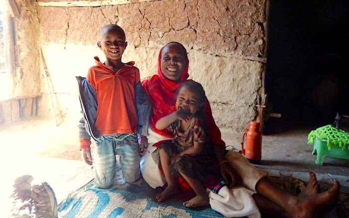 Kelsuma sits with her daughter and son in their modest home