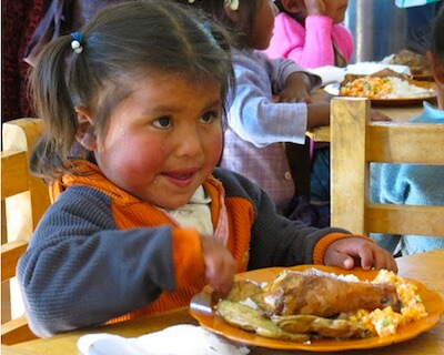 Bolivian girl sitting at a table eating her school meal of chicken and rice