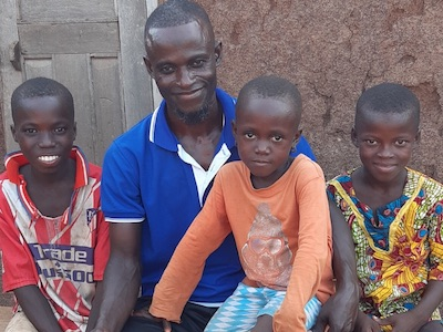 Ahmed sits with three of his four children