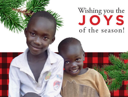 Donate a goat and receive this holiday card showing a smiling African girl and christmas decorations in the background