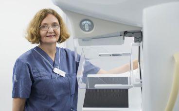 Sköterska vid röntgenapparat för tidig upptäckt av cancer