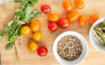 Skärbräda med grönsaker som är bra mat vid cancer