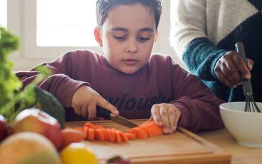 Pojke skär grönsaker som minskar risken för cancer