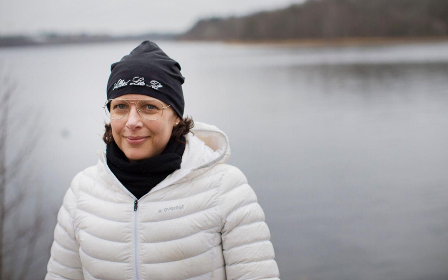 kvinna i vit dunjacka och svart mössa framför sjö i gråmulet väder