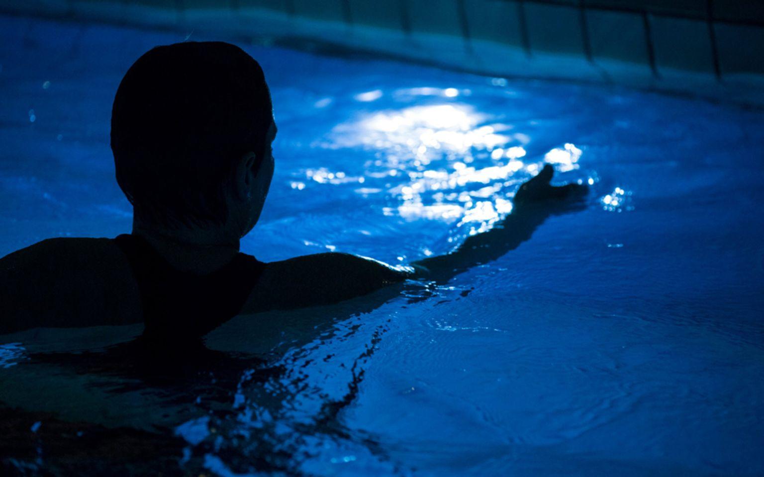 siluett av kvinnas huvud och arm bakifrån i upplyst pool i nedsläckt rum