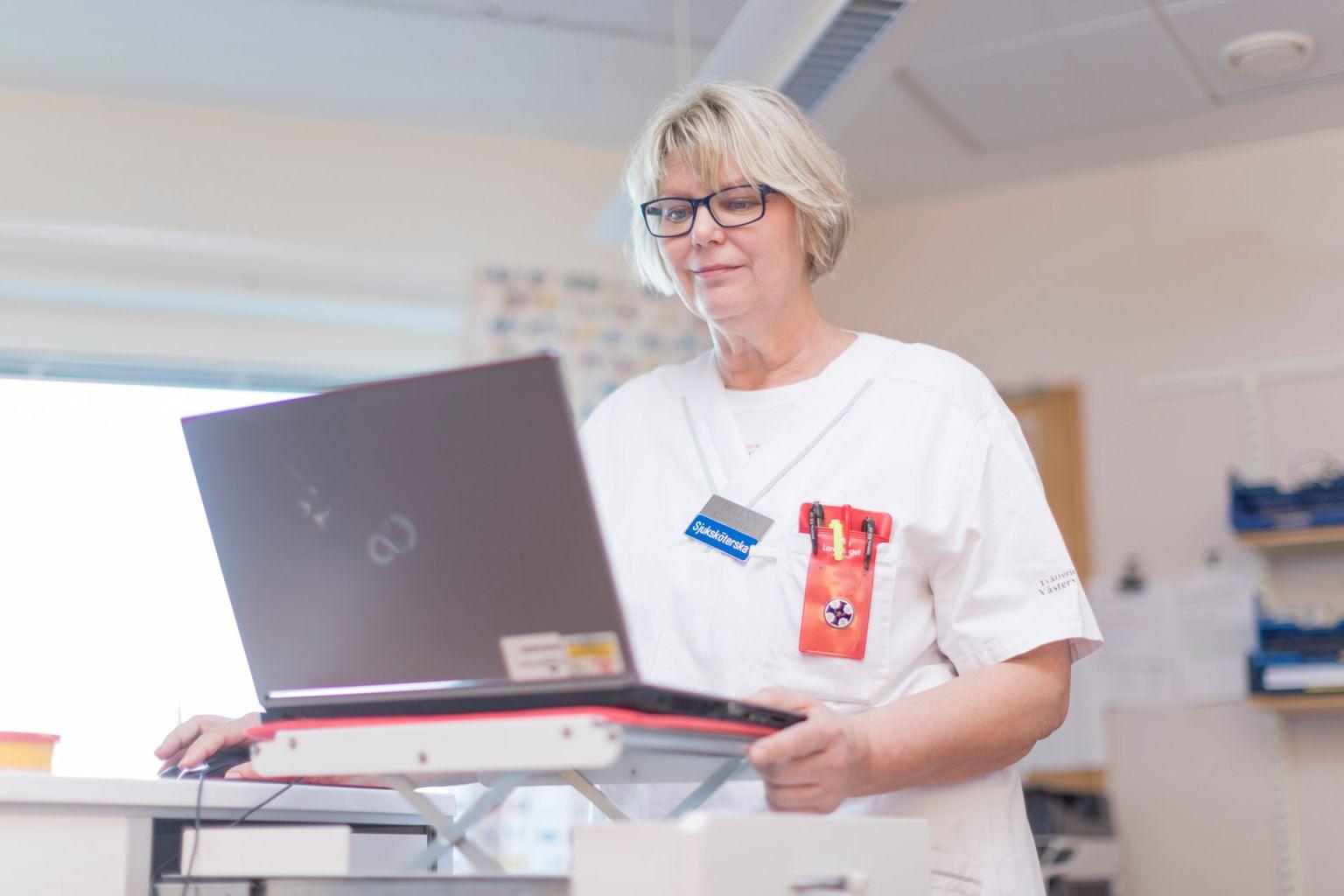blond sjuksköterska vid ståbord med laptop