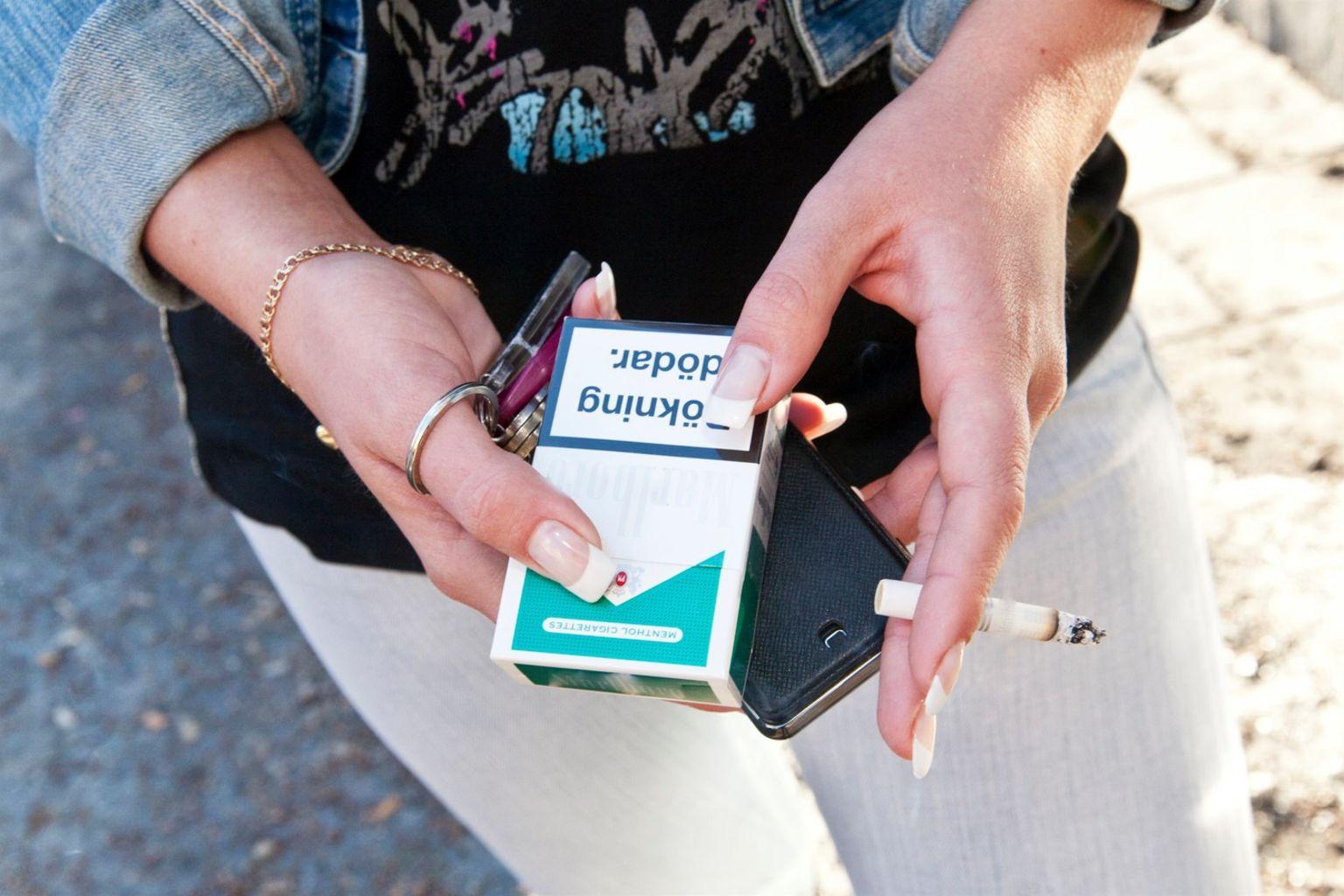 Tjej sitter med ett cigarettpaket i handen