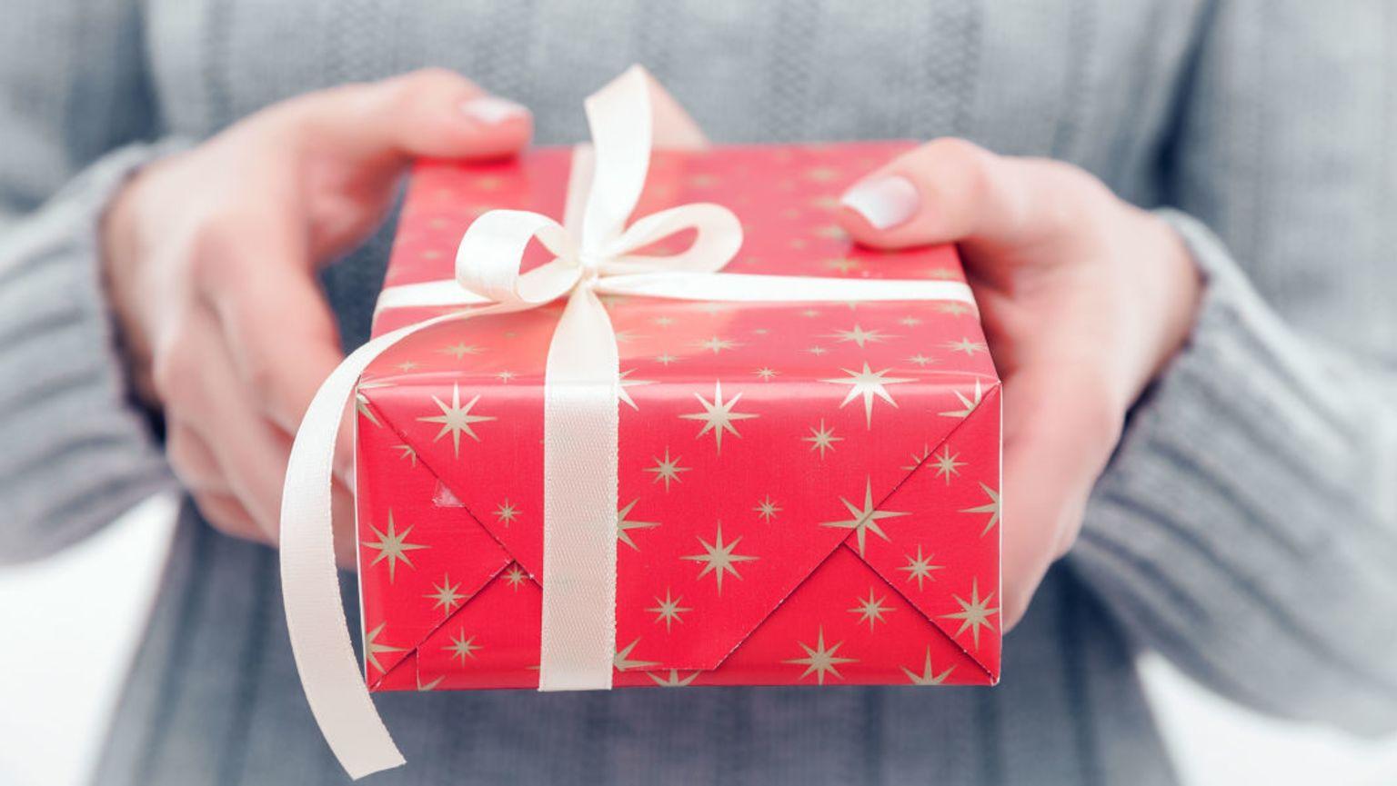 Kvinna med ljusgrå kofta som håller i ett paket, inslaget med rött papper med guldiga stjärnor och vitt presentsnöre.