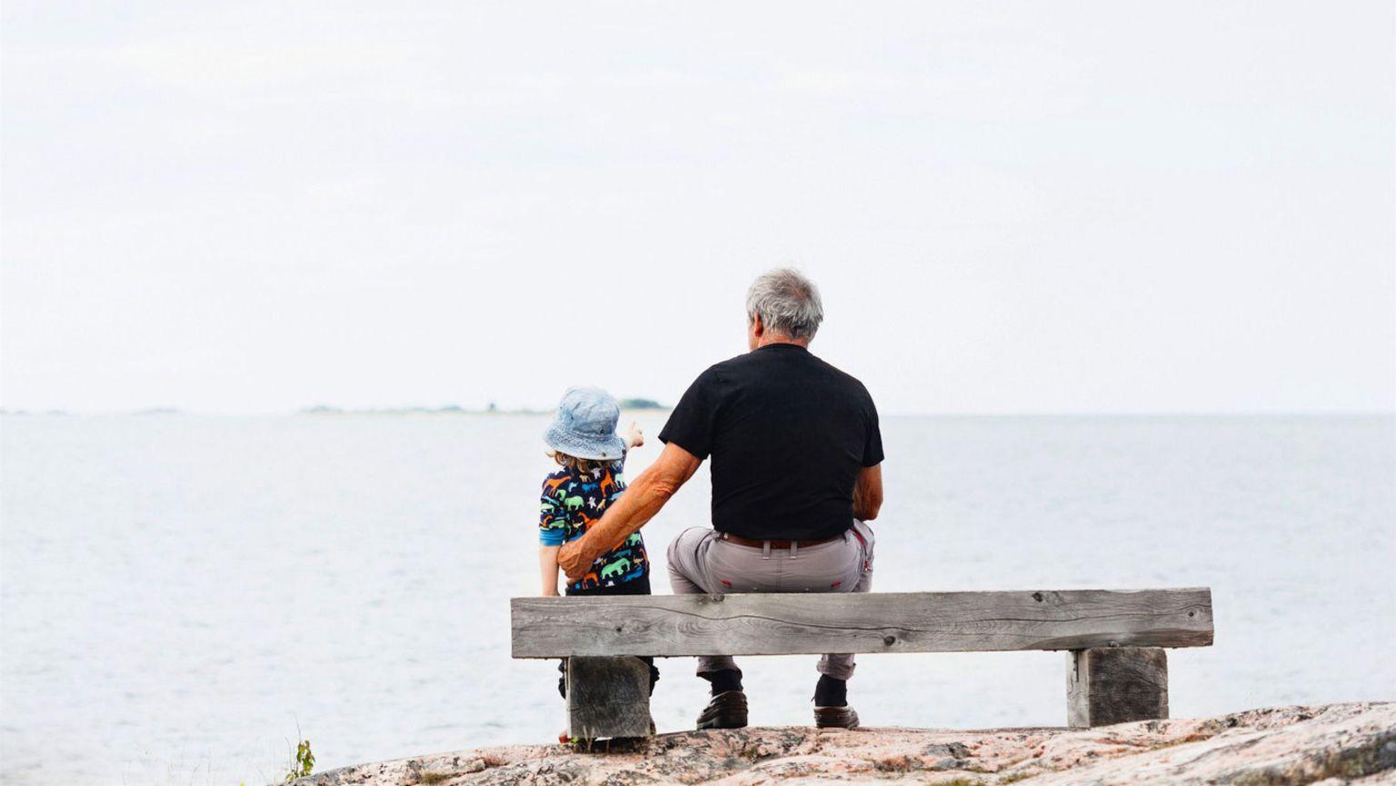 En äldre man och en pojke sitter tillsammans på en bänk mot havet.