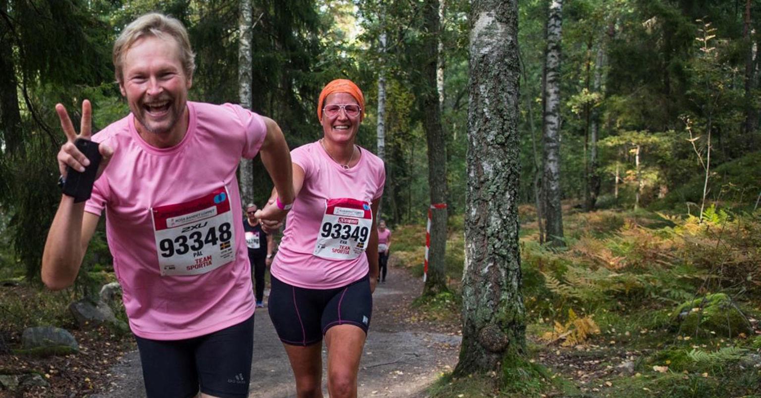 En man och en kvinna i rosa t-shirt, håller varandra i handen samtidigt som de springer upp för en backe.