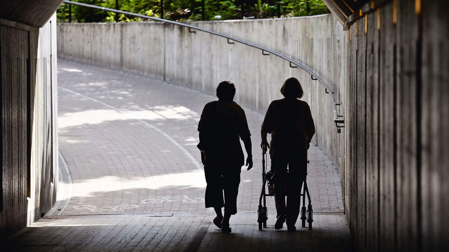 Två äldre kvinnor, en med en rullator, går tillsammans under en viadukt.