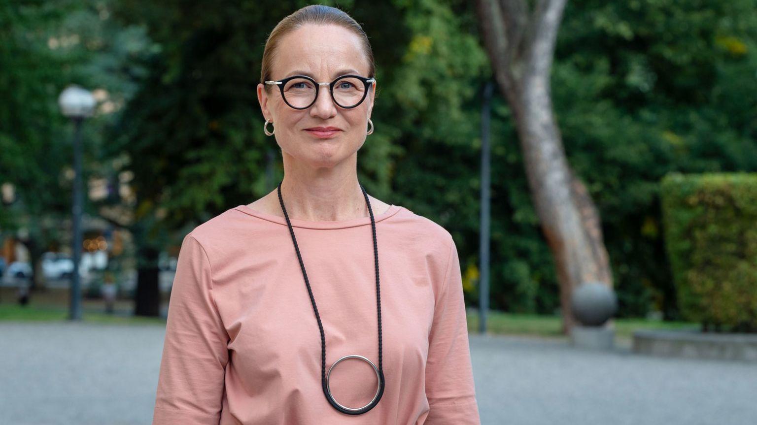 Cancerfondens generalsekreterare Ulrika Årehed Kågström i rosa klänning med en grön lummig bakgrund.