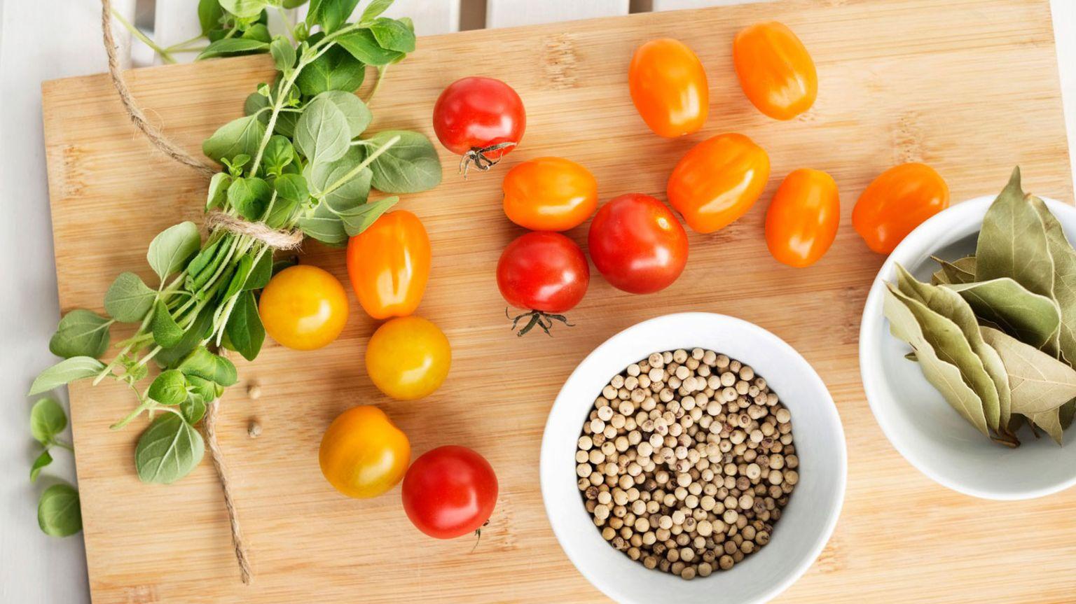 Tomater, färska kryddor och två skålar som är fyllda med lagerblad och peppar.