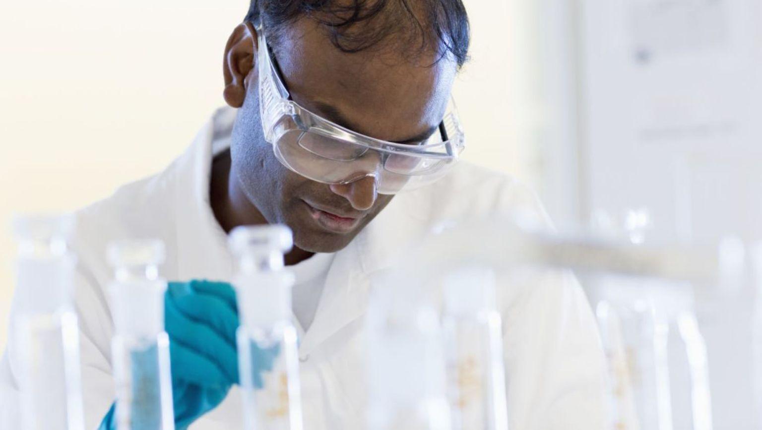 Forskare i ett laboratorium med blå handskar som hanterar prover i provrör.