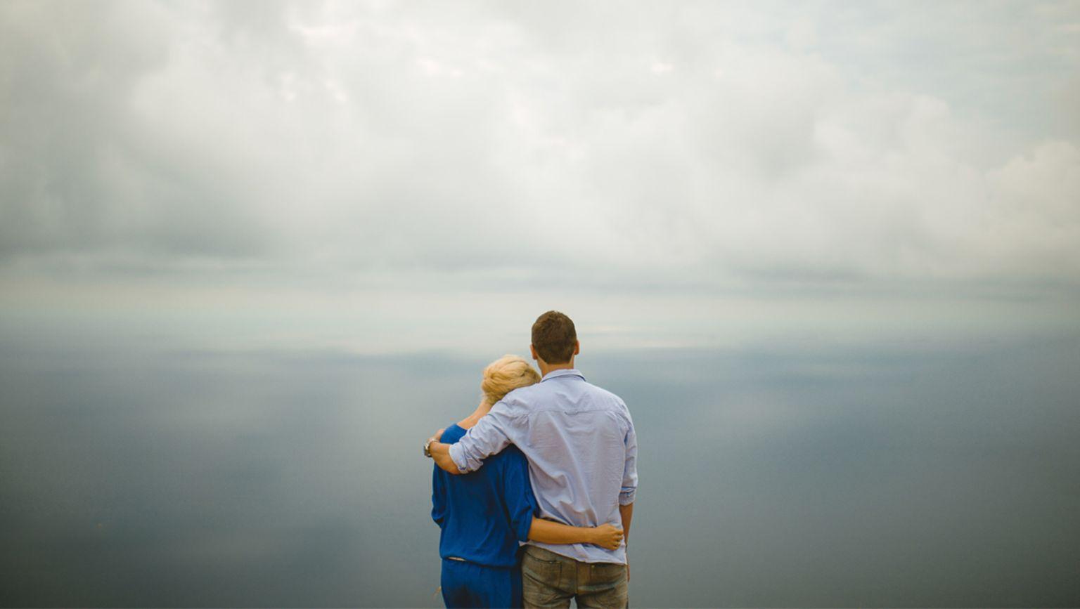 En man och en kvinna håller om varandra och blickar ut över ett dimmigt landskap.