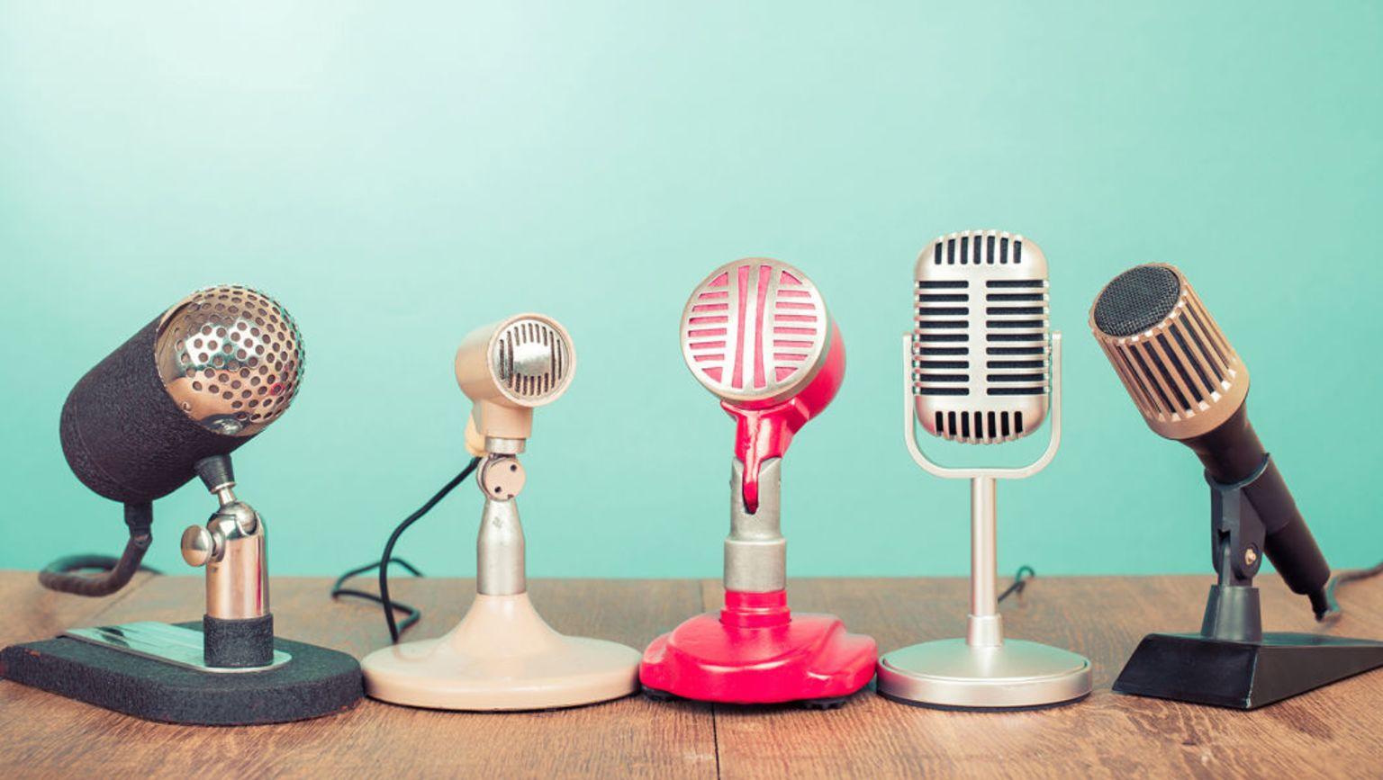 Fem olika typer mikrofoner står uppradade på ett bord.