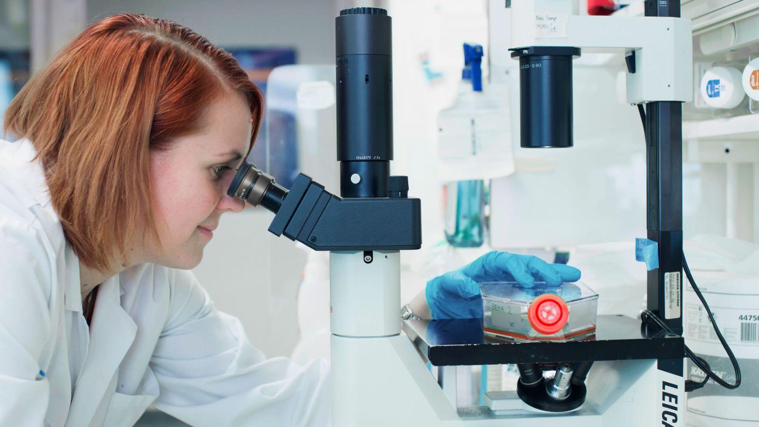 Kvinnlig forskare blickar in i ett mikroskop.