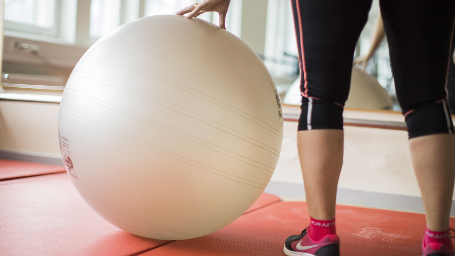 Person i gymnastiksal rullar en stor medicinboll.