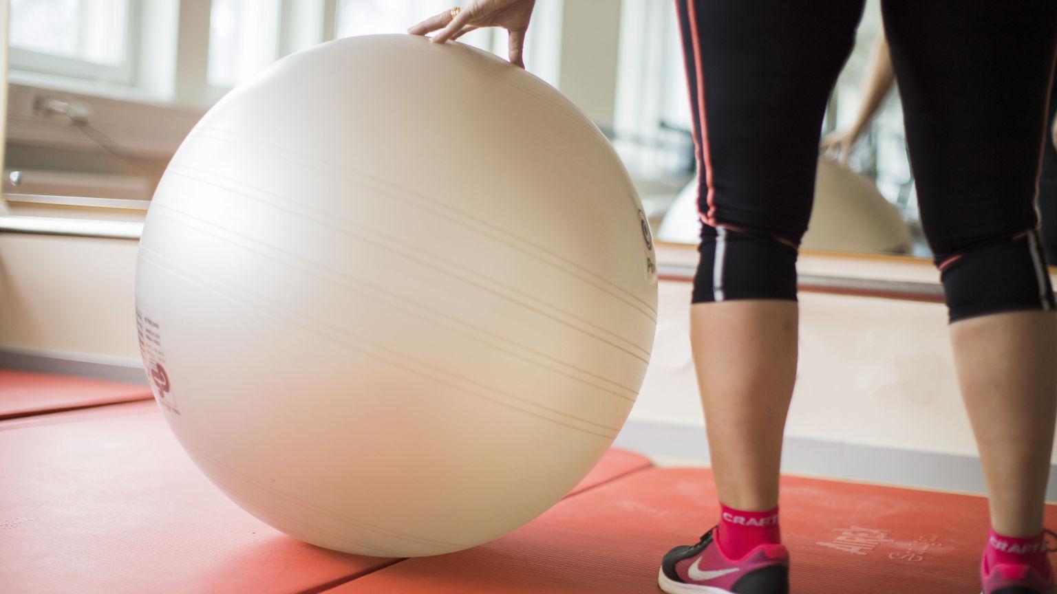 Kvinns står i en gymnastiksal och håller handen på en medicinboll.